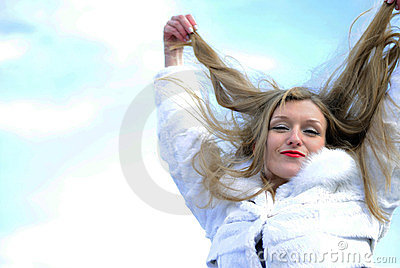 The young beautiful girl in a white fur coat
