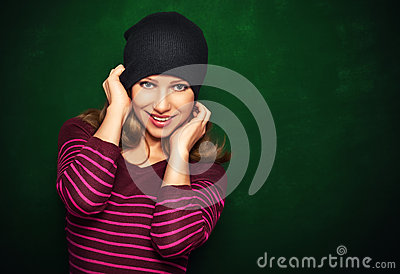 Young beautiful happy girl teenager in a black on a green backgr
