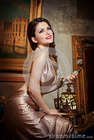 Young beautiful luxurious woman in elegant dress smiling holding a vintage telephone. Beautiful young woman in classic scenery