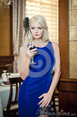Free Young Beautiful Luxurious Woman In Long Elegant Dress. Beautiful Young Blonde Woman In Blue Dress Holding A Glass Of Wine Royalty Free Stock Image - 35607716