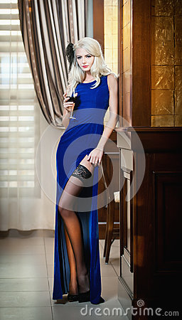 Free Young Beautiful Luxurious Woman In Long Elegant Dress. Beautiful Young Blonde Woman In Blue Dress Holding A Glass Of Wine Royalty Free Stock Photo - 35607745