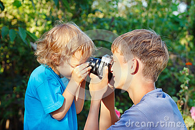 Young beautiful photographers with camera outdoors