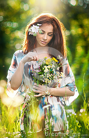Free Young Beautiful Red Hair Woman Holding A Wild Flowers Bouquet In A Sunny Day. Portrait Of Attractive Long Hair Female With Flowers Stock Image - 43395041
