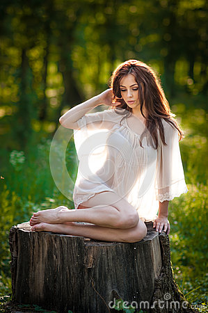 Free Young Beautiful Red Hair Woman Wearing A Transparent White Blouse Posing On A Stump In A Green Forest. Fashionable Sexy Girl Royalty Free Stock Images - 43395039