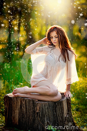 Free Young Beautiful Red Hair Woman Wearing A Transparent White Blouse Posing On A Stump In A Green Forest. Fashionable Sexy Girl Stock Photo - 43395050