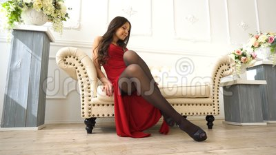 Young beautiful brunette girl in a red dress sitting on the couch in the luxury interior stock video footage