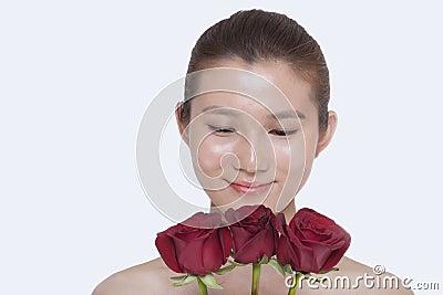 Lebensfreude50 - der zucker ist natürlich also mit fondant enthalten? young beautiful smiling woman looking down bunch red roses studio shot 33397502