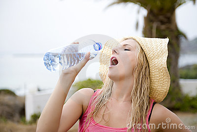 Young beautiful summer woman with bottle of water