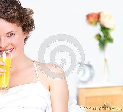 Young beautiful teen drinking juice