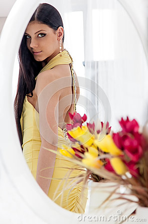 Young beautiful teenager girl looking at her dress in the mirror