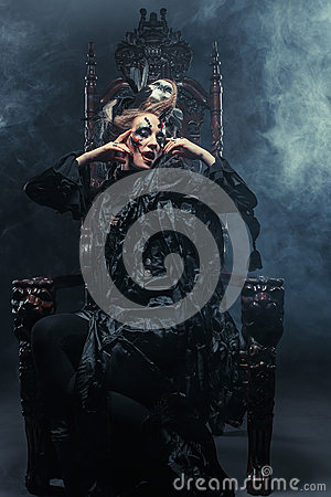 Free Young Beautiful Witch Sits On A Chair. Bright Make Up, Skull, Smoke-  Halloween Theme. Royalty Free Stock Image - 89431896