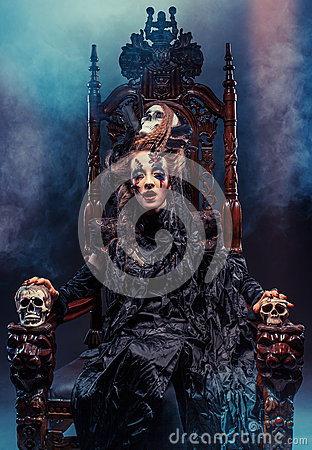 Free Young Beautiful Witch Sits On A Chair. Bright Make Up, Skull, Smoke-  Halloween Theme. Stock Images - 90070054