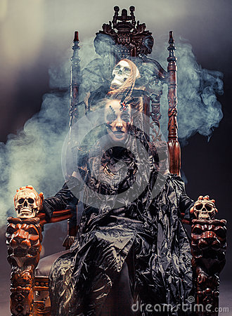 Free Young Beautiful Witch Sits On A Chair. Bright Make Up, Skull, Smoke-  Halloween Theme. Stock Photography - 94266142