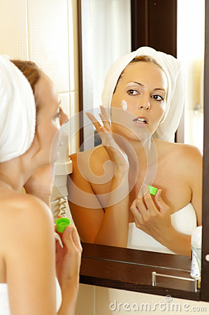 Young beautiful woman applying lotion