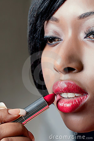 Young beautiful woman applying red lipstick
