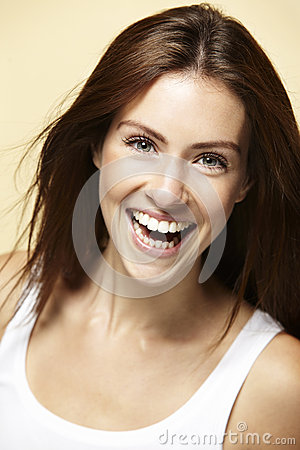Young beautiful woman on beige background, smiling Stock Photo