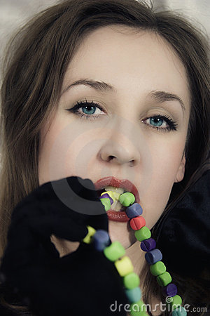 Young beautiful woman Biting multi-coloured beads