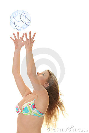Young beautiful woman catching a beach ball