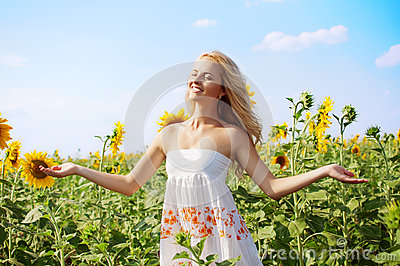 Young beautiful woman on field in summer