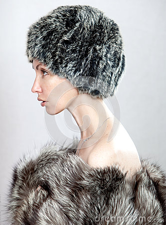 The young beautiful woman in a fur hat in a profil