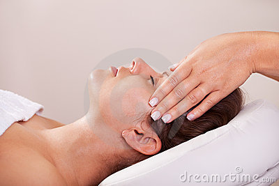 Young beautiful woman getting facial massage
