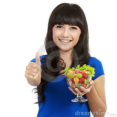 Young beautiful woman holding huge glass of fruits