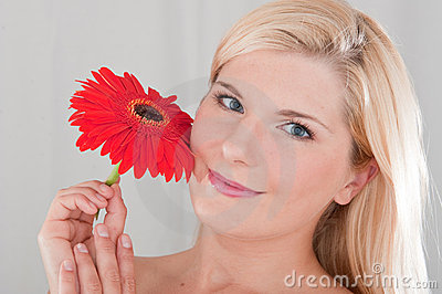 Young beautiful woman holding red flower