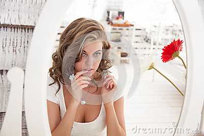 Young beautiful woman looking at her face in the mirror
