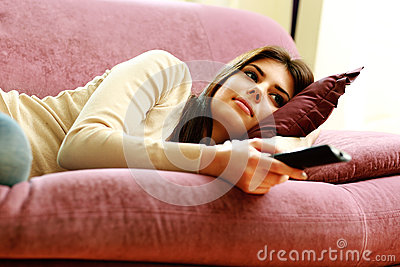 Young beautiful woman lying on the sofa with remote control