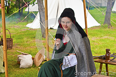 Young beautiful woman in a medieval costume sewing. Editorial Stock Photo