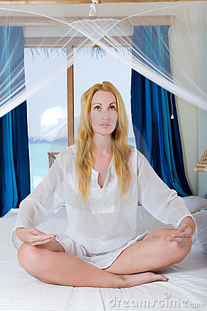 The young beautiful woman meditates on beds, ocean