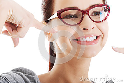Young beautiful woman pointing on her perfect smile.