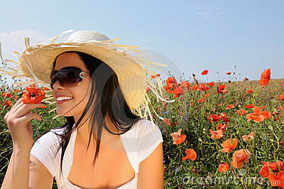 Young beautiful woman in poppy flowers