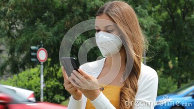 Young beautiful woman with protective mask using smart phone app in city street with traffic cars on the background stock footage