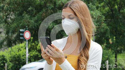 Young beautiful woman with protective mask using smart phone app in city street with traffic cars on the background stock video