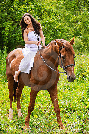 Young beautiful woman rides a horse