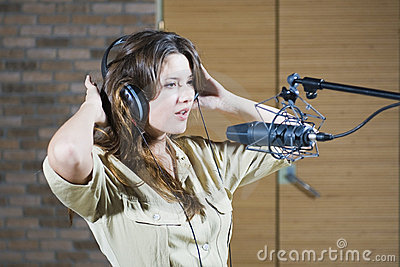 Young beautiful woman singing in microphone