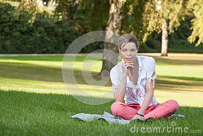 Young, beautiful woman sits on a meadow