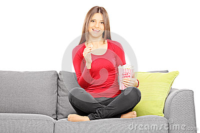 Young beautiful woman on a sofa watching TV and eating popcorn