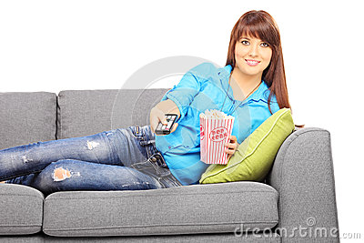 Young beautiful woman on a sofa watching TV