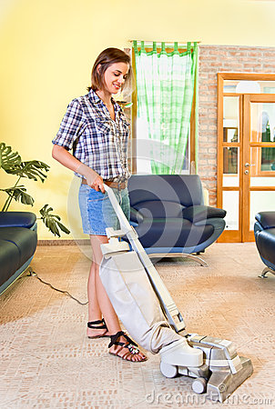 Young beautiful woman with vacuum cleaner at home.