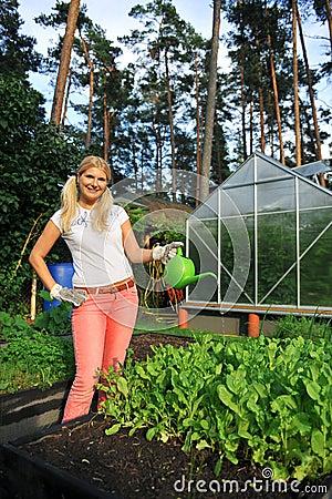 Young beautiful woman working in the garden