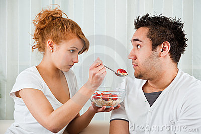 Young, beauty girl feeding a boy strawberry