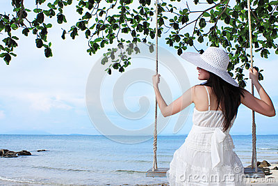 Young beauty lady sitting on rope swings
