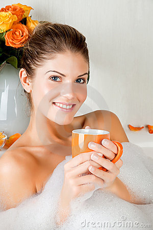 Young beauty woman in the bath drinking herbal tea