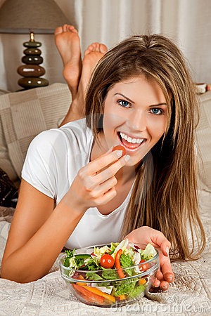 Young beauty woman eating salad