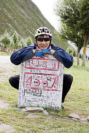 Young bicycle man at destination sign