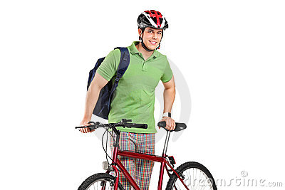 Young bicyclist posing next to a bicycle