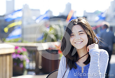 Young biracial teen girl smiling outdoors, sunny background