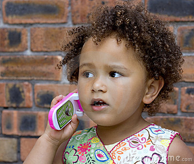 Young black baby girl on a toy cell phone